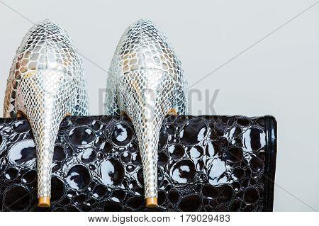 Elegant outfit fashion concept. Black leather shiny handbag and silver high heeled shoes closeup on gray. Studio shot.