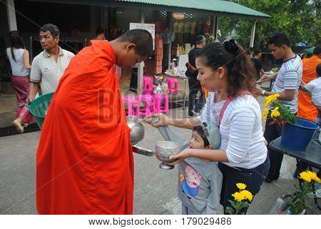 November 5, 2016 :  Mother and son give food to the monks nearby Mon bridge area / Nong Lu, Sangkhla Buri District, Kanchanaburi