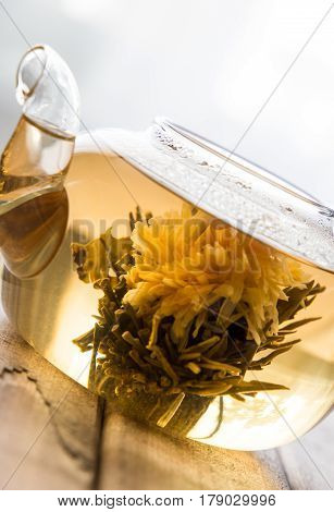 a glass tea pot with Flower Chinese tea on light wooden background in front of the window. vertical