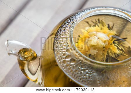 top view closeup of a glass tea pot with Flower Chinese tea on light wooden background