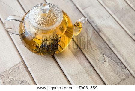 a glass tea pot with Flower Chinese tea on light wooden background. space for text