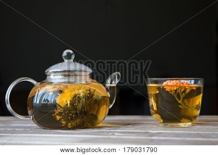 a glass tea pot with Flower Chinese tea and a cap of green tea on light wooden table in front of dark background. vertical