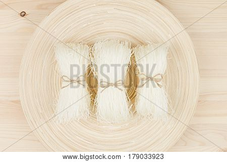 Sheafs raw asian cellophane noodles on plate on beige wooden board top view.
