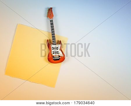 Slip of paper reminders with electric guitar miniature.