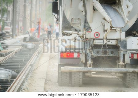 Cement truck on a busy construction site with sand and cement.