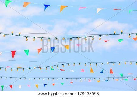 Triangle colorful flags decoration at party or temple fair with blue sky background