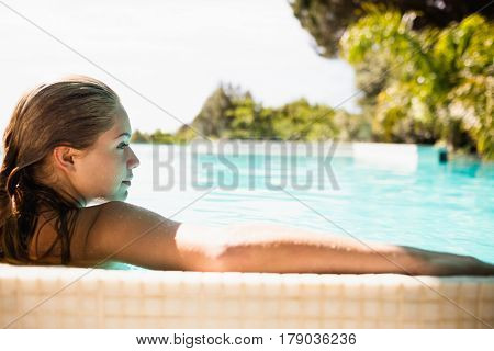 Rear view of blonde relaxing in the pool