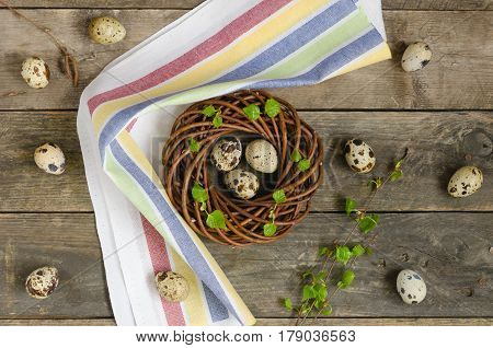 Wreath with three quail eggs is in the center on a wooden background. Easter concept. Still life