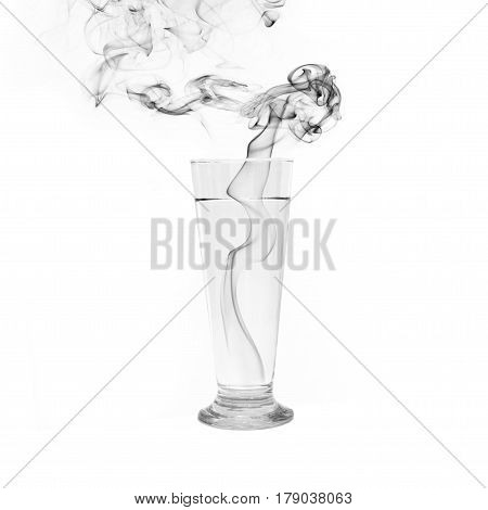 Glass of water with black smoke on white background.