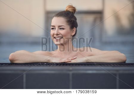 Happy young woman enjoying a relaxing swim standing in a swimming pool resting her hands on the tiled surround grinning as she looks to the side