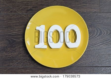 The number one hundred on the yellow plate and brown background.