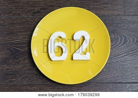 The number sixty-two on the yellow plate and brown background.