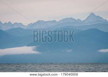 Blurred light blue landscape of hills, clouds and Baikal lake