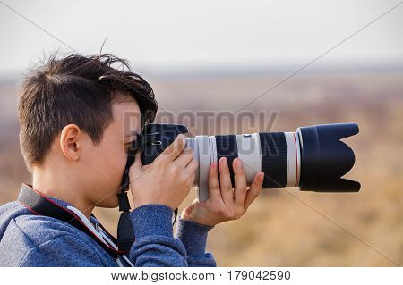 Young male photographer with telephoto in nature