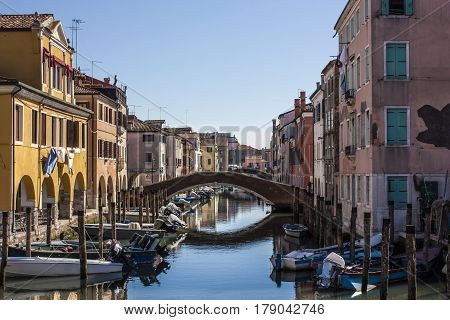 A typical landscape of Chioggia Italian city in the Veneto lagoon near Venice. A bridge over water with half a multitude of boats of transport typical of this area ...