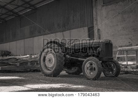 Old abandoned tractor in a shed. Full of dust and dirt left to itself was old and outdated.