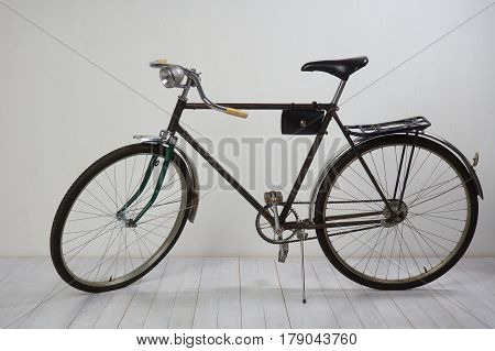 Old bike on white wooden floor and white textured wall
