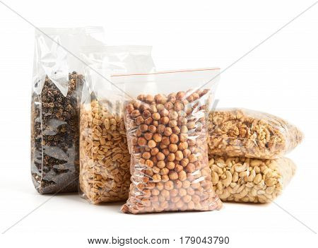 Dried fruits and nuts in transparent package over white from left to right: dried mulberry roasted and salted peanuts hazelnuts walnut and cashew on the bottom