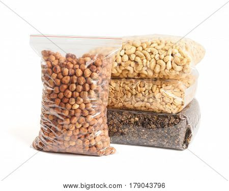 Dried fruits and nuts in transparent package over white: hazelnuts cashew roasted and salted peanuts dried mulberry.