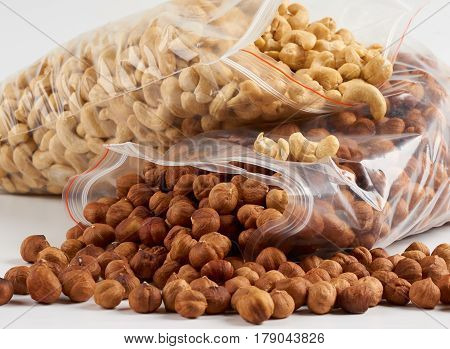 Closeup of cashew and hazelnuts in opened transparent zipper plastic bags over white