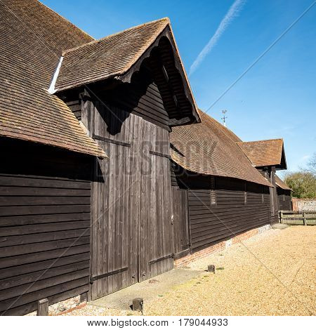 Old English Farm Barn. The exterior of an old timber barn on an English farm in the bright spring sunshine.