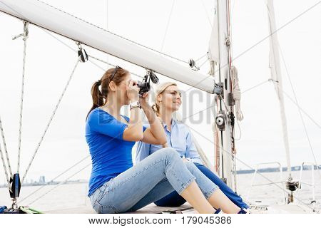 Two beautiful, attractive young girls taking pictures on a yacht. Traveling, vacation, tourism, concept.