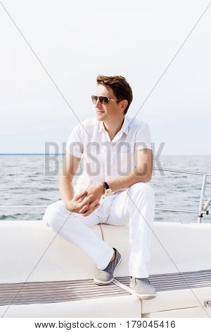 Handsome man sitting on deck of a yacht and enjoying the views. Traveling, vacation, concept.