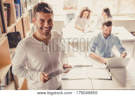 Successful young business people are working in office. Guy in the foreground is using a digital tablet looking at camera and smiling