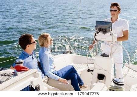 Happy and beautiful couple having a rest on yacht and watching captain driving a boat. Traveling, tourism, journey, concept.