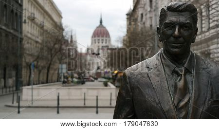 A close viwe of Ronald Reagan Statue face with Parliament building in the background in Budapest