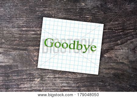 Goodbye Text On A Checkered Note. Wooden Background