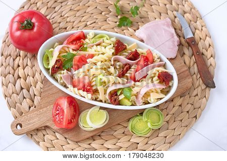 Raw pasta gratin with ham and vegetable.