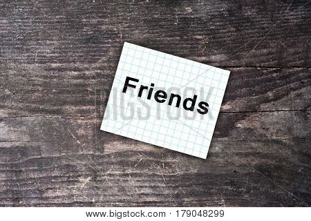 Friends Text On Checkered Paper Note. Dark Wooden Background