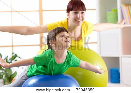 mother doing gymnastics with daughter childon fitness ball