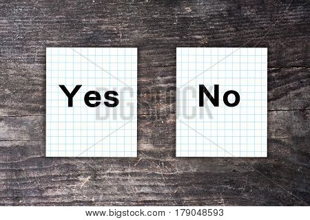 Yes And No Text On Checkered Paper Notes. Dark Wooden Background. Make A Choice