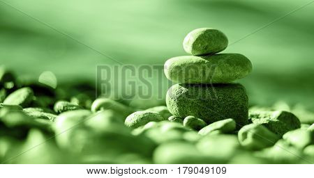 Website banner of Zen balancing pebbles on the beach in green