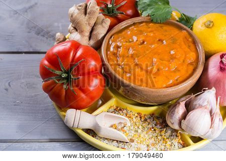 Bowl of vegetable Tikka Masala sauce and ingredients that go into making it - red tomatoes chili pepper carrot coriander leaves onion garlic gember. Used widely in Indian food.