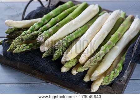 Fresh spring green and white asparagus ready to cook on wooden backgroung close up