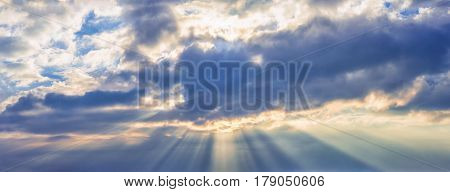 background panorama. rays of the sun make their way through dramatic clouds