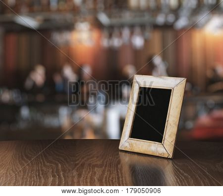 old photo frame on the wooden table on table in a night club