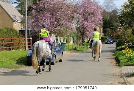 Fulwell Road Finmere Oxfordshire United Kingdom March 26 2017: Female riders and horses on village road wearing Please Pass Wide & Slow sign on fluorescent jacket Oxfordshire UK