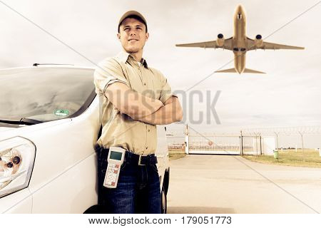 a delivery person is standing next to his white van. in the background, a freight airplane is taking off.