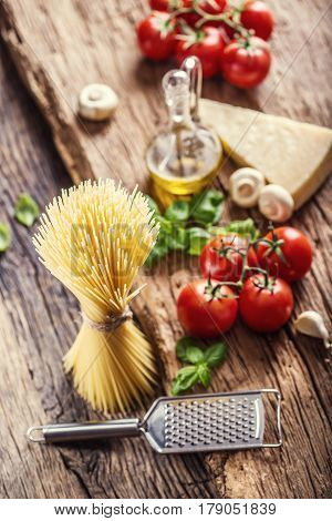 Spaghetti.Spaghetti tomatoes basil olive oil parmesan cheese and mushrooms on very old oak board. Mediterrannean cuisine and ingredients.