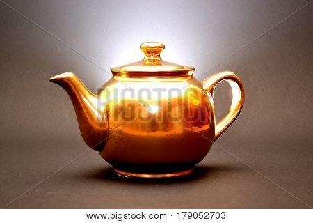 golden teapot shines on a dark background