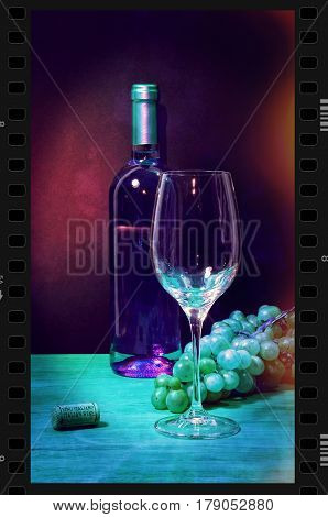 White wine bottle in strip film frame with glass and bunch of grapes on the wooden table