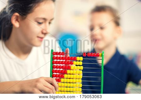 Cute little brother and sister playing with colorful abacus at home