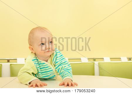 little baby sits at a table and waits. small beautiful child boy attentively looking