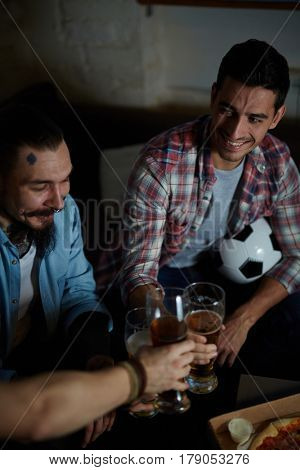 High angle portrait of group of friends meeting at home, sitting on couch in dark room toasting with beer and eating pizza while watching football match on TV