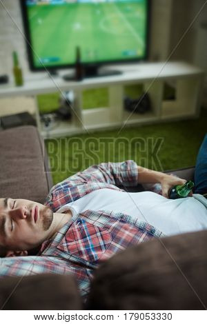 Young man falling asleep on couch with beer while watching football match on television set