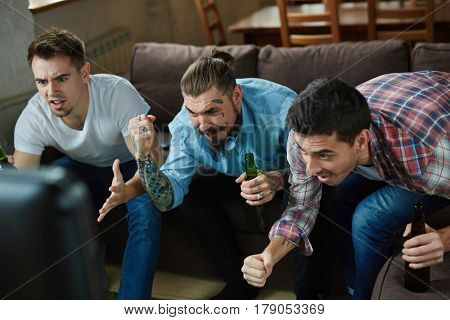 Portrait of three emotional adult men watching sport match on TV and cheering  with excitement while sitting on couch in living room with beer
